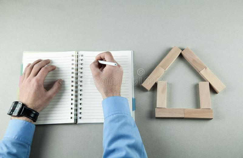 Man writing on notepad. House model made of wooden blocks stock photography
