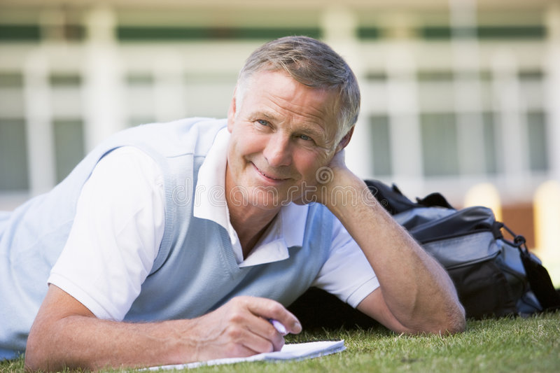 A man writing notes while lying on a campus lawn.  royalty free stock photography
