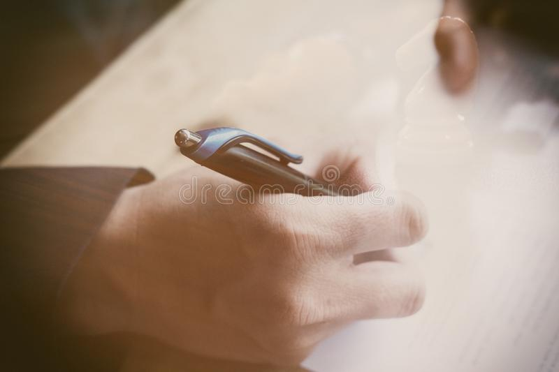 Man writing on paper document in office. Businessman or job seek royalty free stock photography