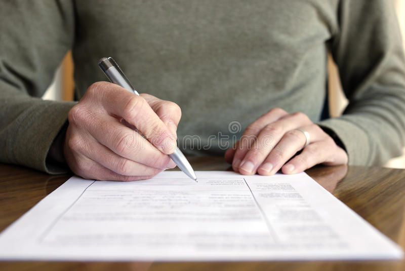 Man Writing on Paper with Pen on Table stock images