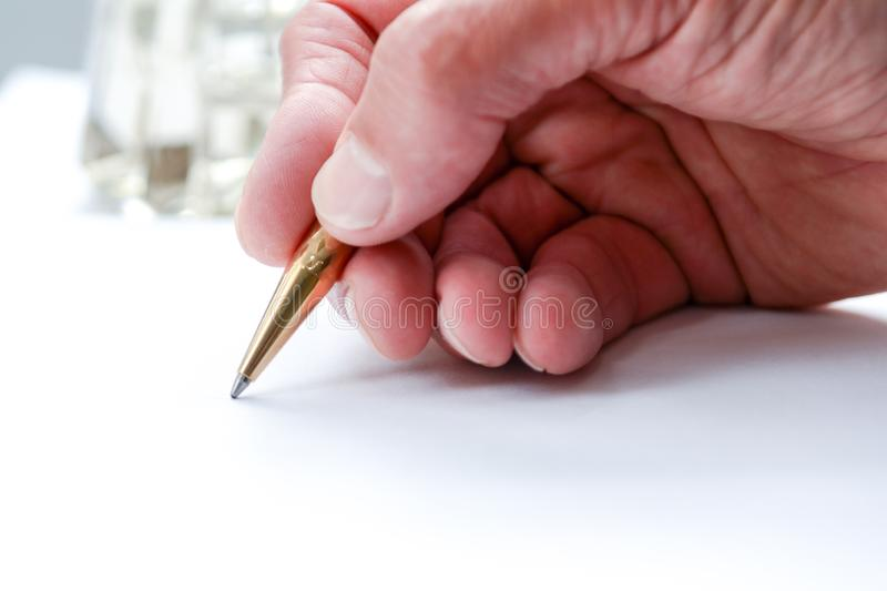 Man writing with pen on paper, close up of hand hollding pen to write on paper document stock image