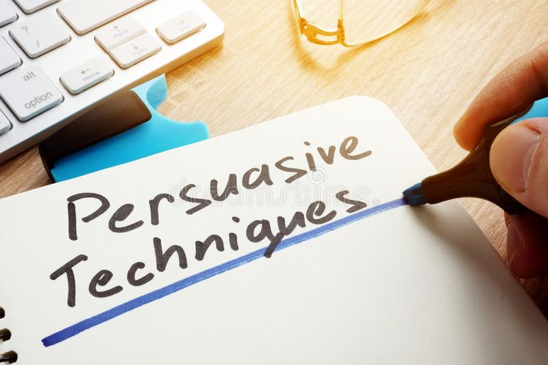 Man writing Persuasive Techniques in a note. Man writing Persuasive Techniques in a notepad royalty free stock photos