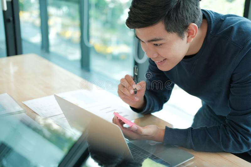 Man writing reminder on sticky note. male freelancer student working organizing plan at workplace. Startup man writing reminder on sticky note. male freelancer royalty free stock image