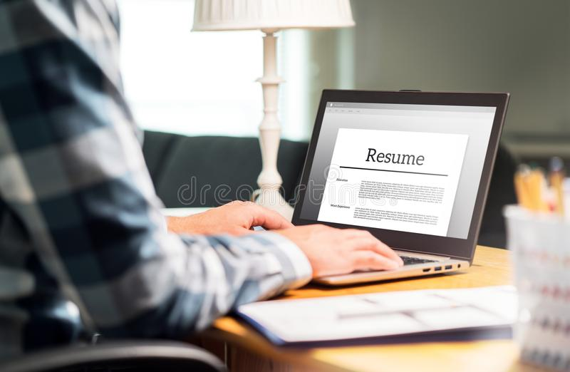 Man writing resume and CV in home office with laptop stock image