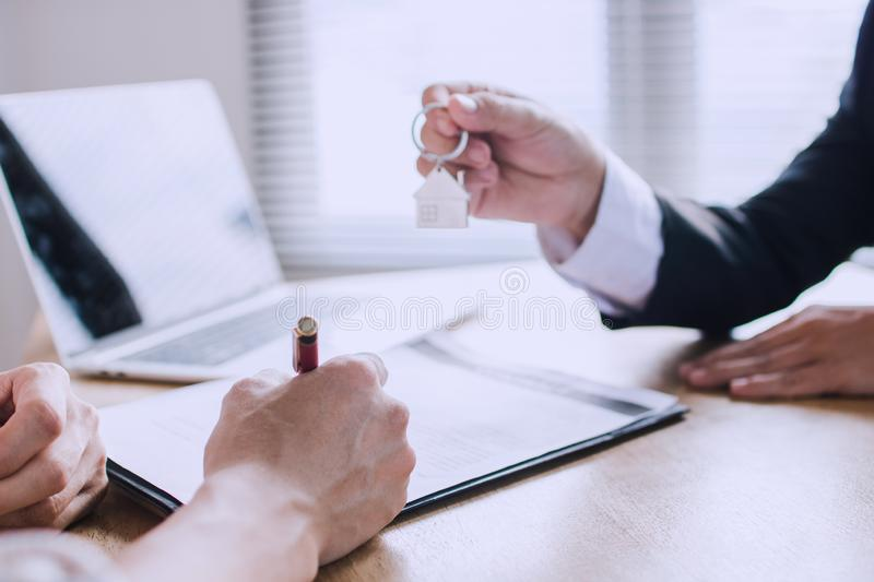 Man writing and sign on contract of house after finishing selling and buying home with home agency banker royalty free stock images