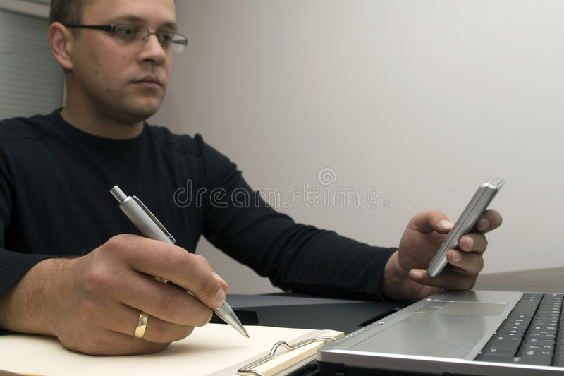 Man writing and texting. A view of a man sitting in front of a laptop computer, writing on a clipboard and sending a text message on a cellphone stock images