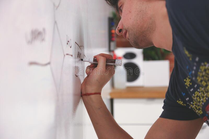 Man writing on whiteboard royalty free stock image