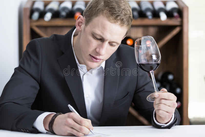 Man writing on a wine tasting sheet. Young man is writing down on a wine tasting sheet on a wine tasting session holding a red wine glass at a restaurant royalty free stock images