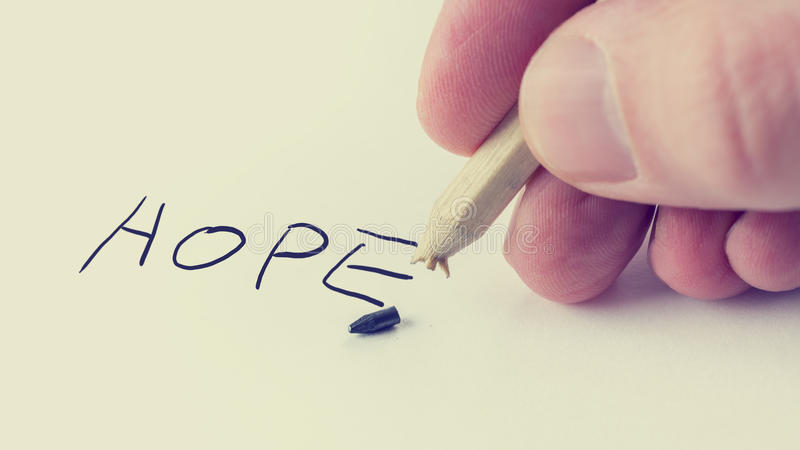 Man writing the word Hope on notepaper. Retro image of a man writing the word Hope on notepaper with a pencil on which the graphite point has just broken with stock images