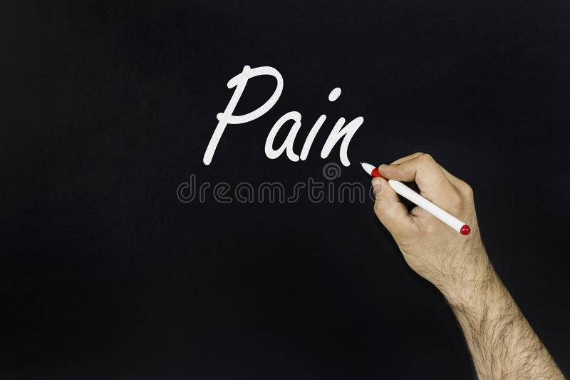 Man writing the word pain on a blackboard royalty free stock image