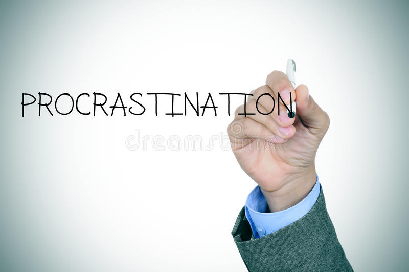 Man writing the word procrastination. Closeup of the hand of a man writing the word procrastination in the foreground royalty free stock photo