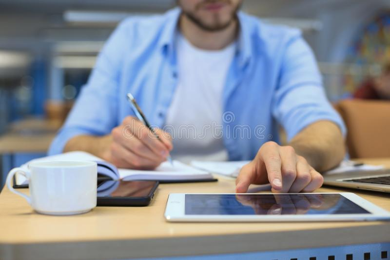 Man writing work plan with pen on paper notebook, browsing internet on digital tablet on office desk.  royalty free stock photo