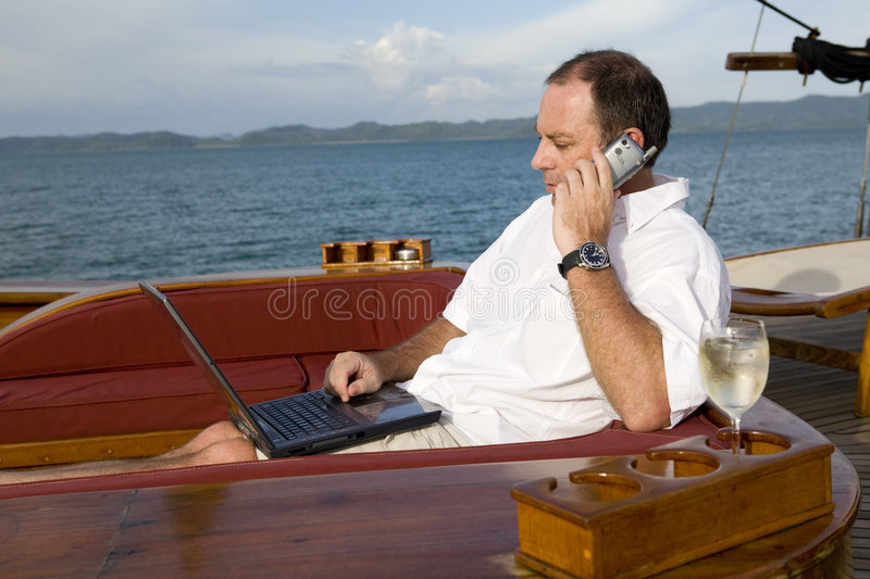 Man on yacht with phone and laptop stock photos