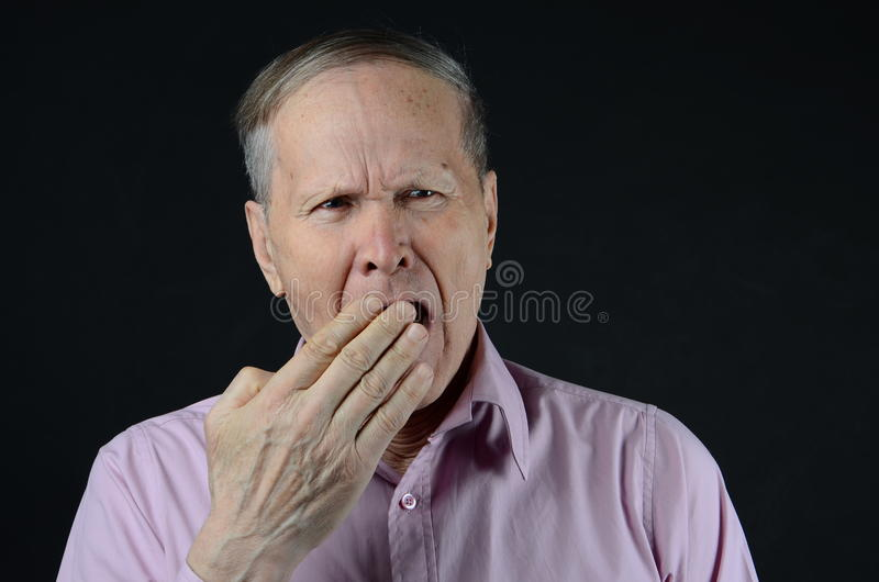 Man yawning with hand closing his mouth stock photography