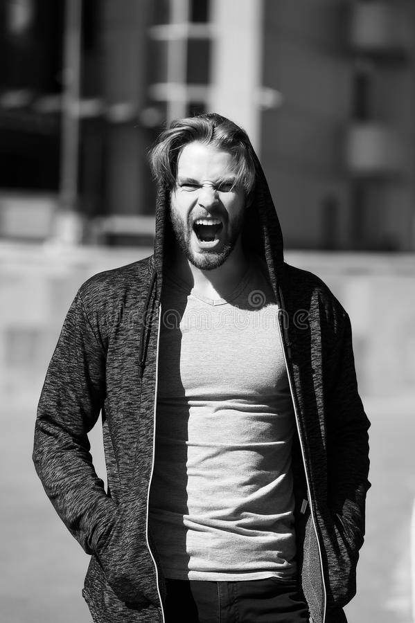 Man yawning with hood on head. And grey tshirt on sunny morning outdoors on streetscape. Sportswear and fashion. Sportswear and fashion. Leisure, sporty style royalty free stock photos