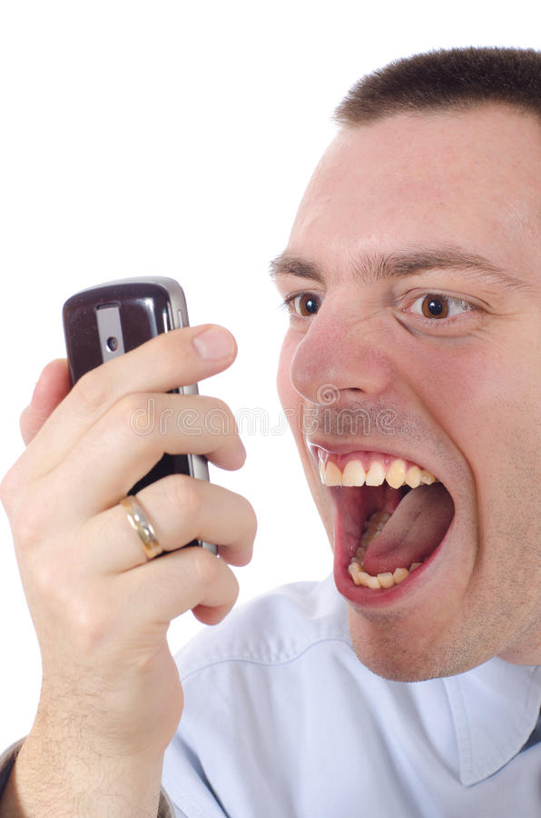 Man Yelling at the phone. Young man, looking angry and frustrated, yelling on a cellular phone in his hand stock image