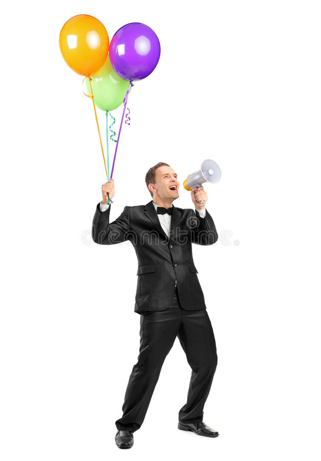 Man yelling throw a megaphone and holding balloons royalty free stock photo