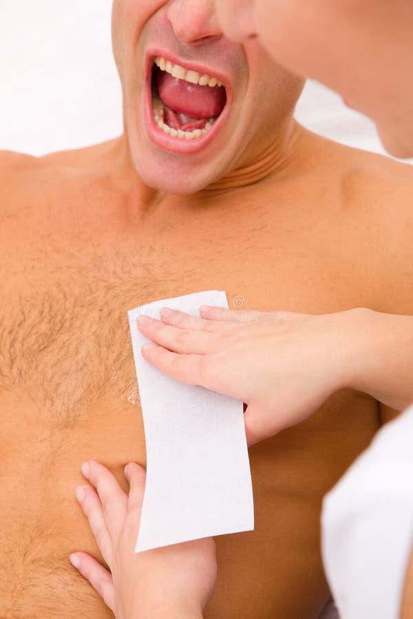 Man yelling while waxing. Torso on spa saloon royalty free stock photo
