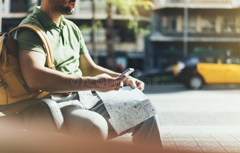 Man with yellow backpack holding smartphone, tourist looking map city on background taxi, hipster planning route using in hands. Mobile phone, traveler connect stock images
