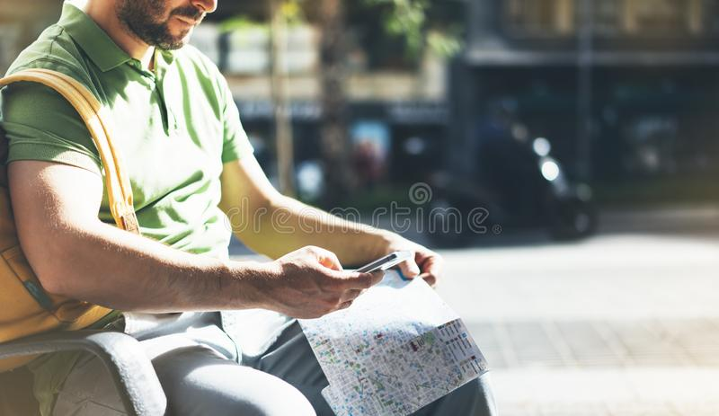 Man with yellow backpack holding smartphone, tourist looking map city on background taxi, hipster planning route using in hands royalty free stock photography