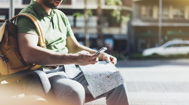 Man with yellow backpack holding smartphone, tourist looking map city on background taxi, hipster planning route using in hands stock images
