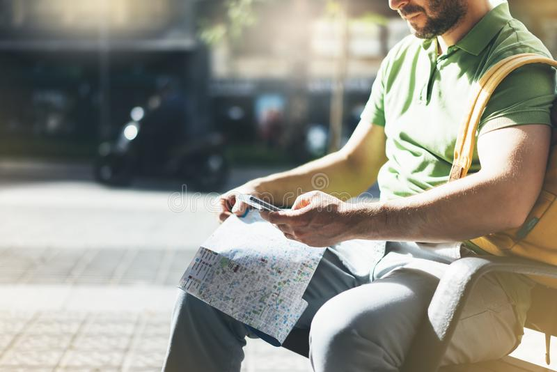 Man with yellow backpack holding smartphone, tourist looking map city on background taxi, hipster planning route using in hands stock photo
