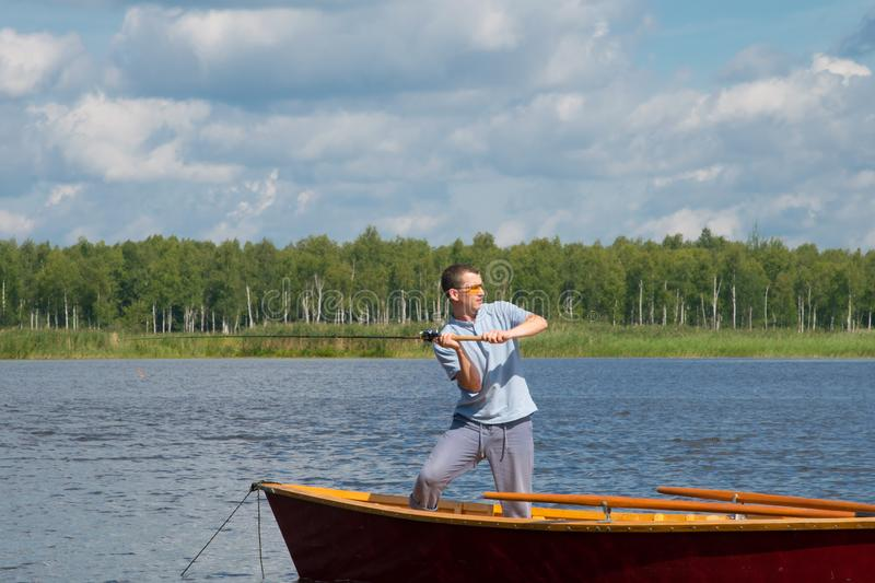 A man in yellow glasses, in a boat, in the center of the lake, throws a fishing pole to catch a big fish, against the backdrop of. A beautiful landscape stock images