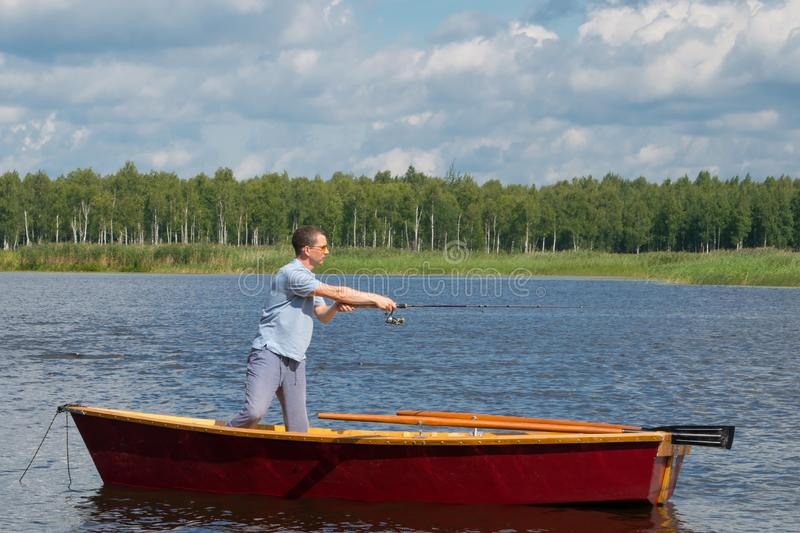 A man in yellow glasses, in a boat with oars, in the center of the lake, holds a fishing pole to catch a big fish, amid a royalty free stock photos