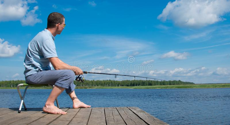 A man in yellow glasses, sitting on the pier, holding a fishing rod, against a beautiful landscape stock photo