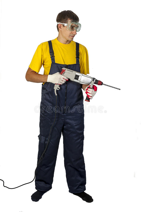 Man in yellow shirt in coveralls with the drill on an white background stock photo