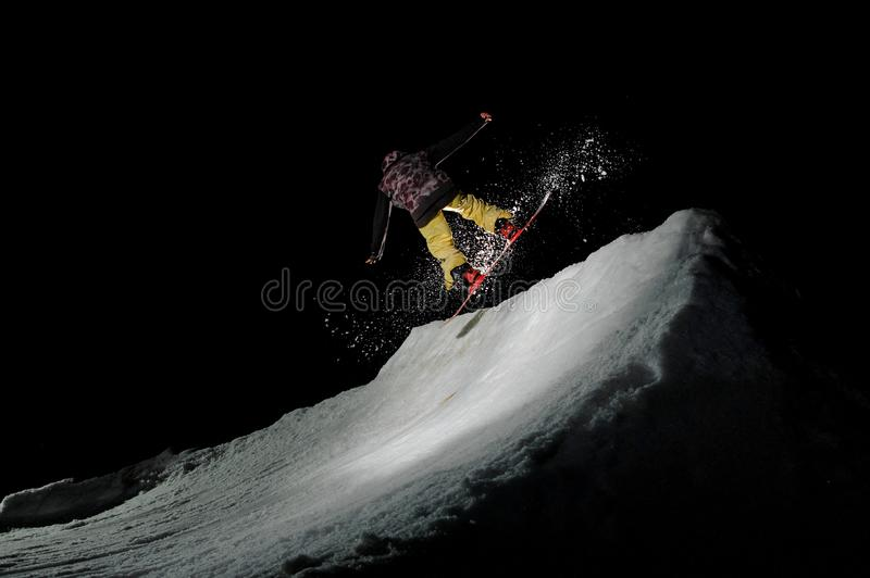 Man jumping on a snowboard against the dark sky stock photography
