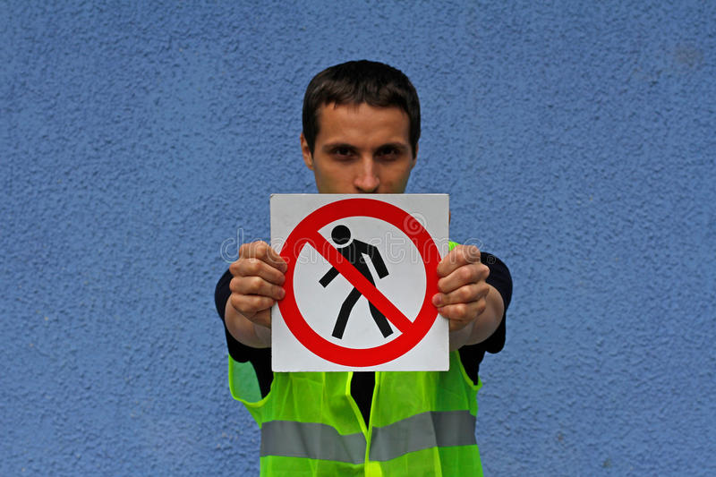 Man in a yellow waistcoat holding sign `No entry` stock photos