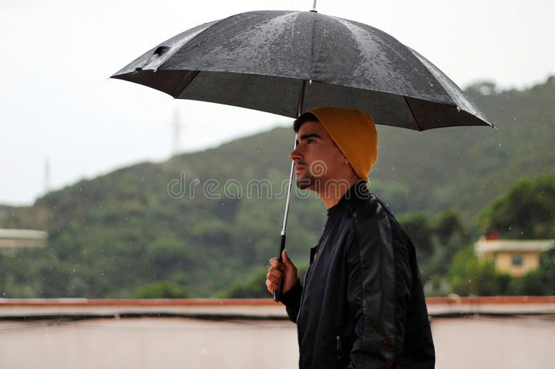 Man with a yellow wool cap and a leather jacket holds open black umbrella in his hand under the rain. Behind the boy lies the mountain royalty free stock photos
