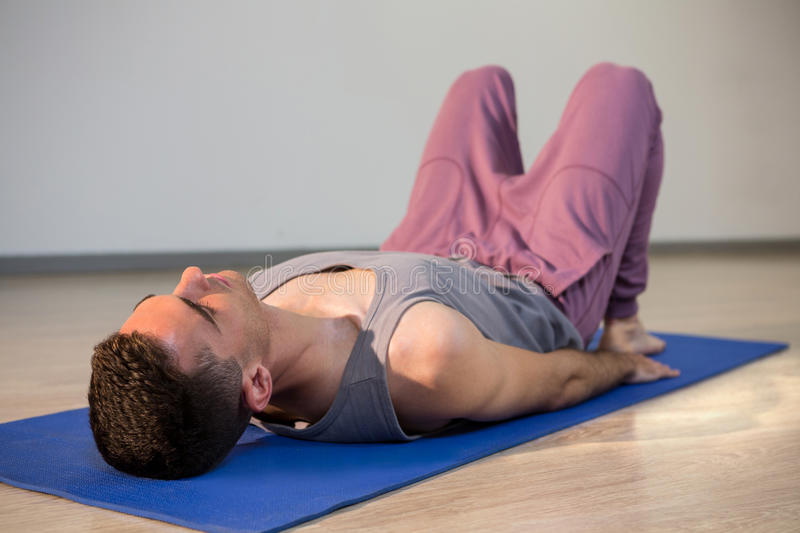Man in yoga corpse pose. In gym royalty free stock photos