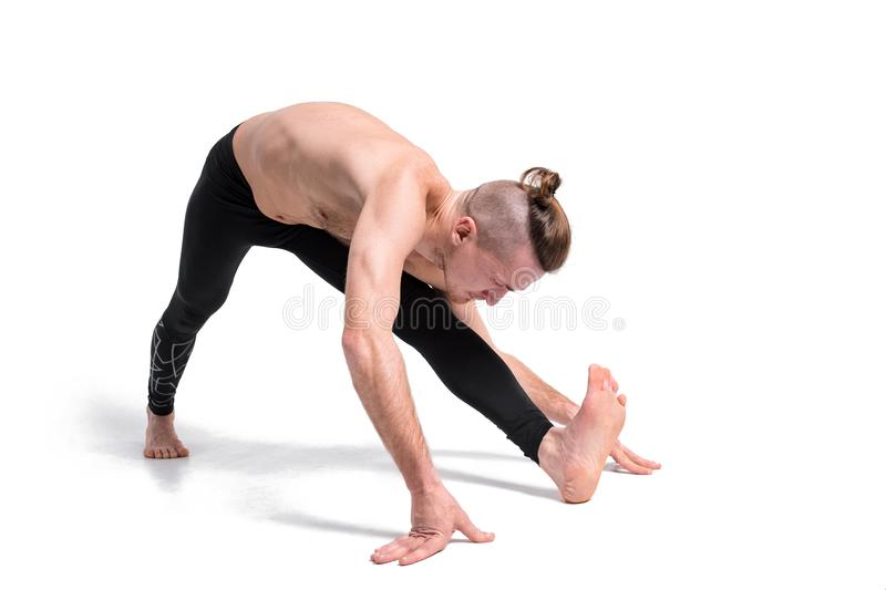 Man in yoga pose doing yoga exercises. Studio shot over white ba royalty free stock photo