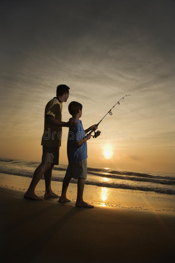 Man and young boy fishing in surf royalty free stock photos