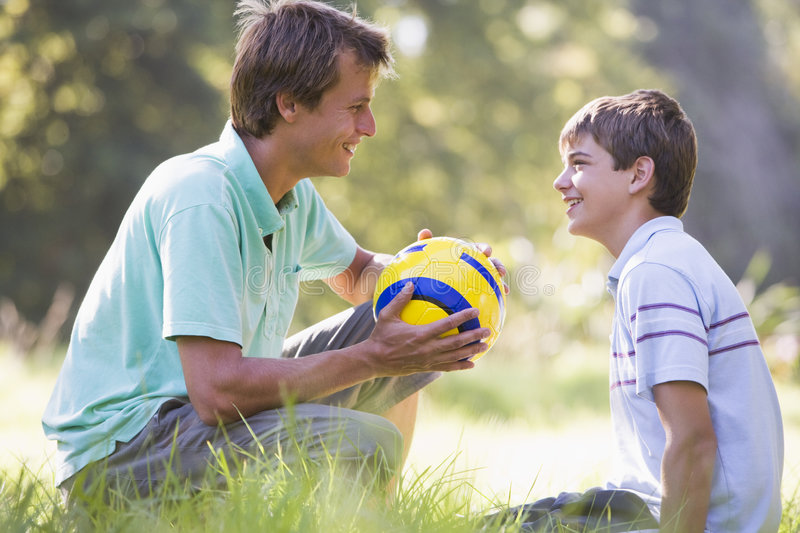 Man and young boy with soccer ball smiling royalty free stock images