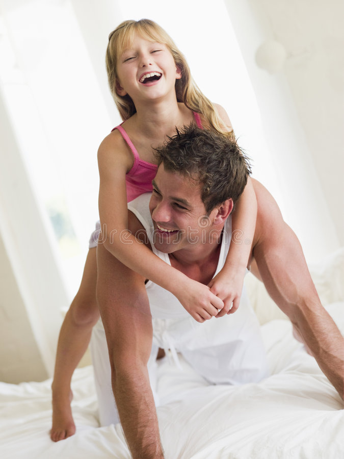 Man and young girl in bed playing and smiling