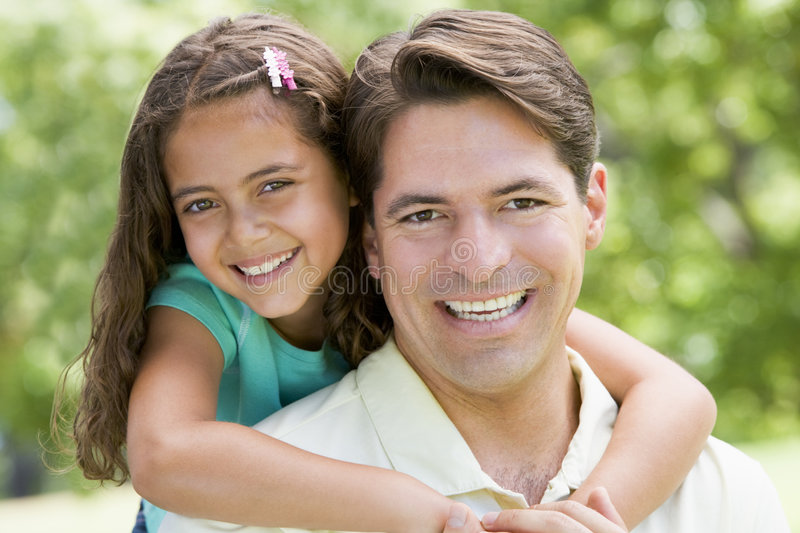Man and young girl embracing outdoors smiling stock image