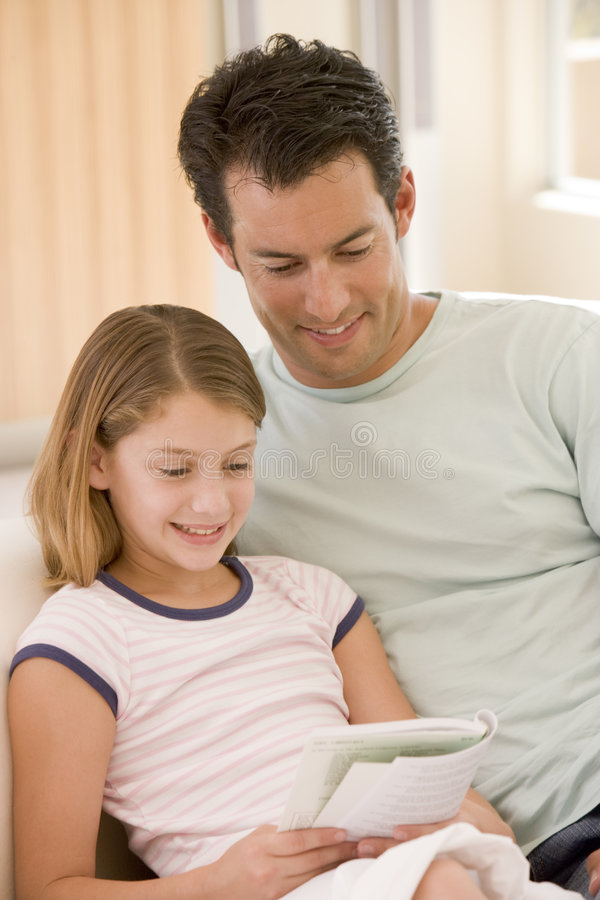 Man and young girl in living room reading book stock image