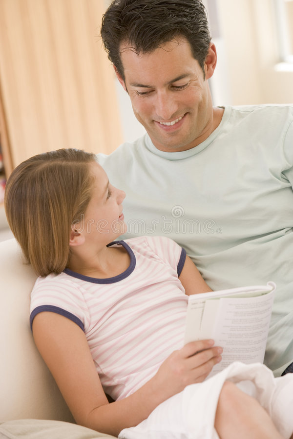 Download Man And Young Girl In Living Room Reading Book Stock Photo - Image: 5775286