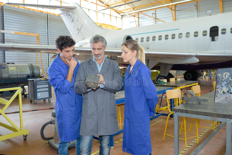 Man with young people in aircraft hangar royalty free stock photos