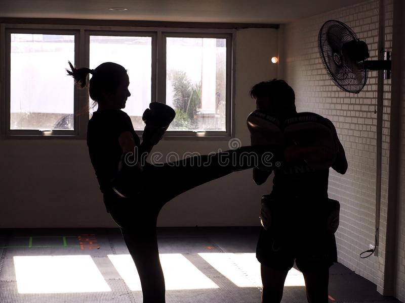 Man and young woman fighting together. Female practicing boxing. Fit woman and her trainer boxing indoors. Portrait of young stock photo