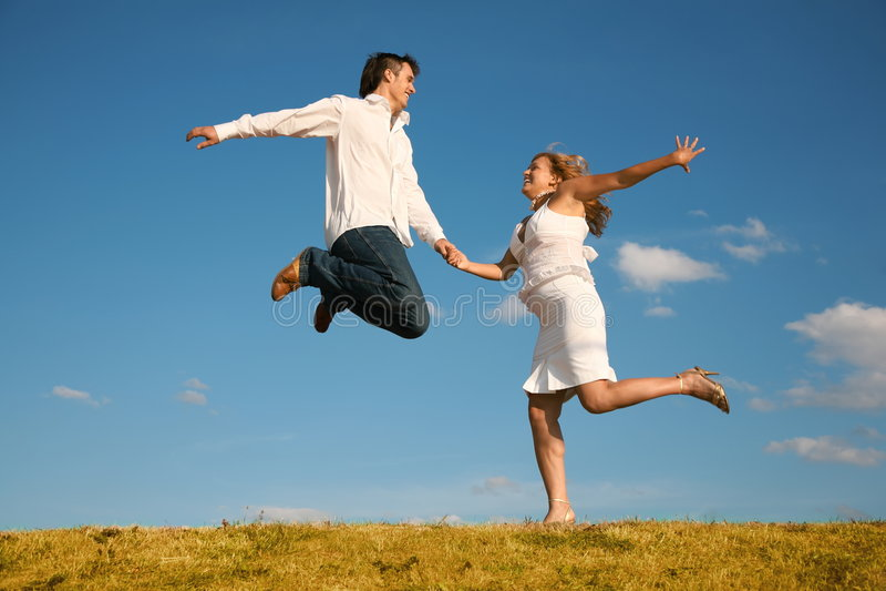 Man and young woman jumping stock photos