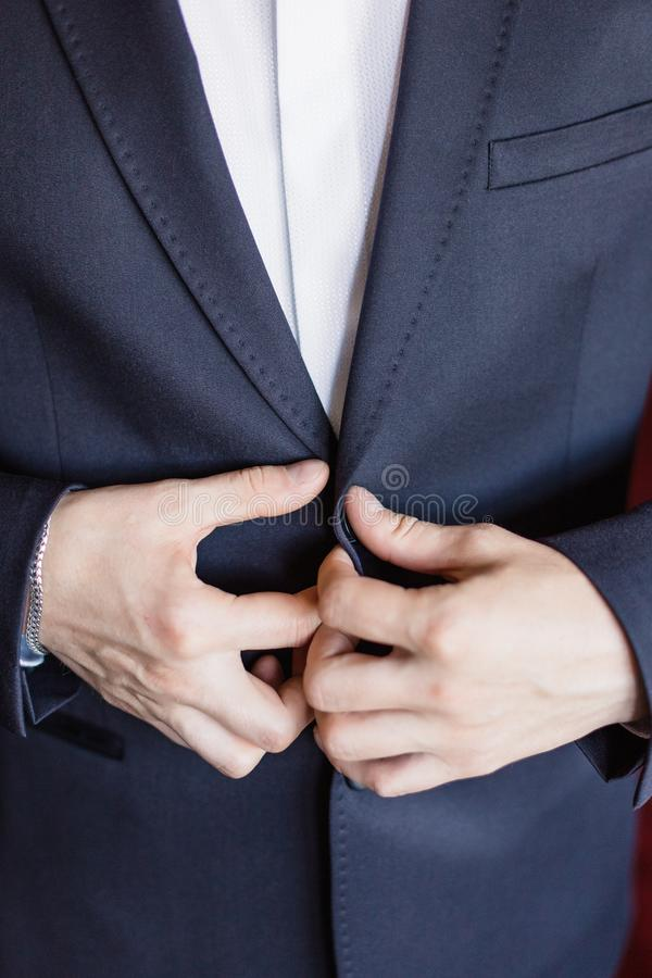 The man zips up his jacket, groom in a jacket, white tie, bridegroom`s fees, business style. stock photography