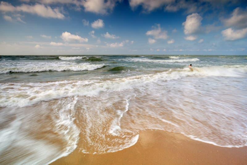 Man zwemt in de Noordzee golven in de zomer royalty-vrije stock foto
