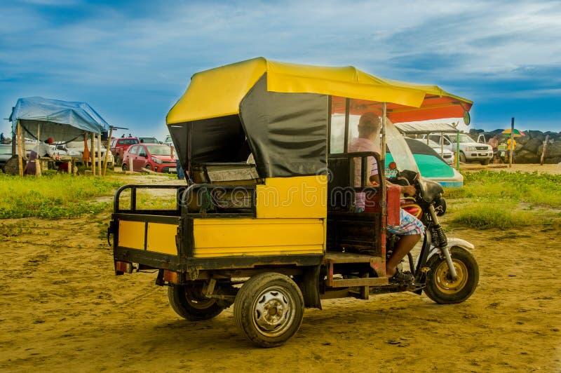 MANABI, ECUADOR - MEI 29, 2018: Niet geïdentificeerde mens die zijn driewieler over het gele zand drijven en van mooi genieten royalty-vrije stock foto's