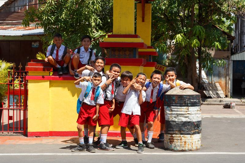 Students in uniform, Manado Indonesia. Manado, Indonesia - August 04 2015: Group of young students in uniform pose for tourist in street of Manado on North royalty free stock image
