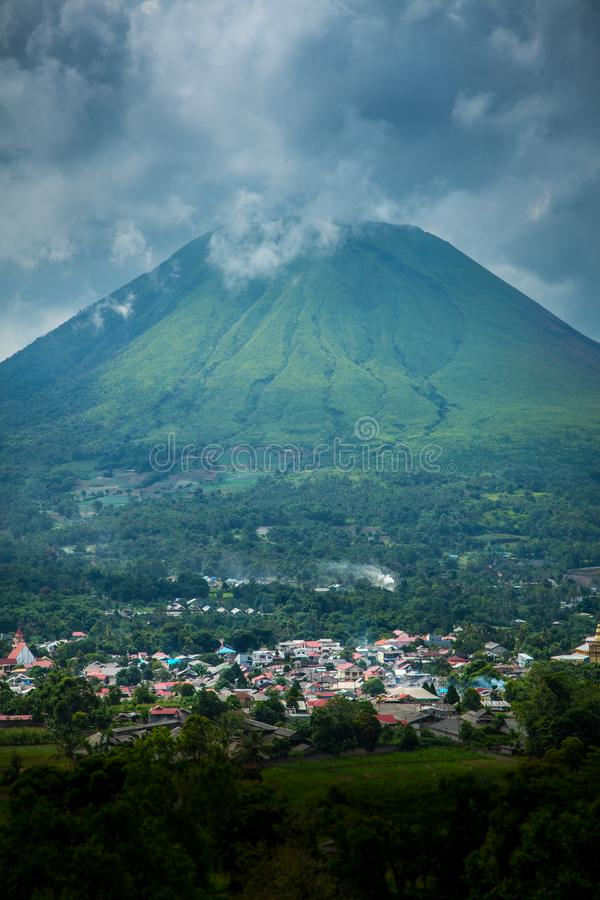 Manado, Indonesia in valley of volcano. Aerial view of Manado, Indonesia in valley of volcano with cloudy skies royalty free stock photography