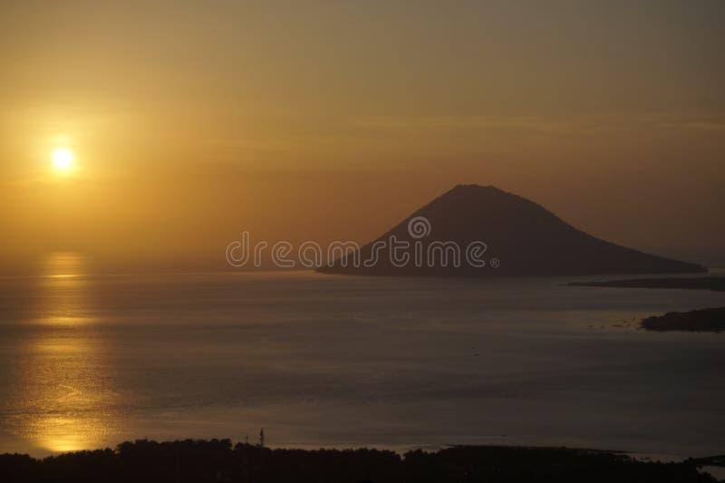 Manado Tua con el fondo de la puesta del sol de Tumpa imagenes de archivo